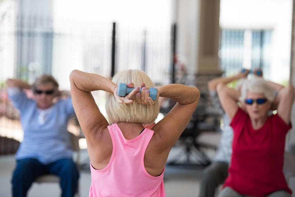Senior exercise class holding weights behind head