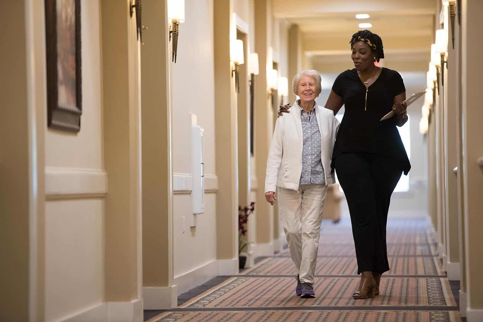 Staff member walking with senior woman